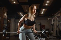 与轻的重量的年轻女人举的杠铃在健身房 健身女性做的crossfit锻炼 库存图片