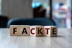 与轻碰的木立方体在对事实词的块伪造品在桌背景 新闻、解答和企业概念 库存照片