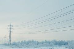 与输电线的冬天风景 免版税库存照片