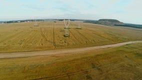 与输电线的电力驻地在与庄稼的领域附近 影视素材