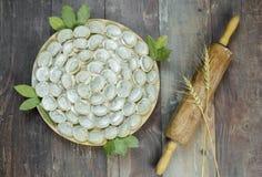 与辗压别针的肉饺子俄国pelmeni在木背景 图库摄影