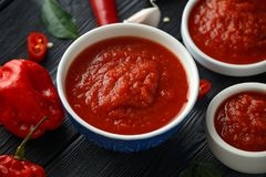 与辣椒、大蒜和蕃茄的混合的辣热的甜辣味番茄酱在土气木背景 免版税库存照片
