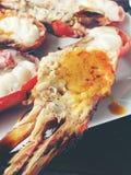 与辣椒和荷兰芹片断的可口烤巨型河虾在白色盘用酱油在小碗在中心,求爱 库存照片