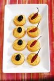 与辣椒粉乳酪奶油的薄脆饼干,装饰用红色意大利辣味香肠 库存图片