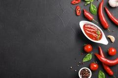 与辣椒调味汁和不同的香料调味汁瓶的平的位置构成  库存照片
