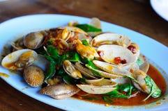 与辣椒酱和蓬蒿叶子的油煎的蛤蜊 免版税库存图片