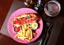 与辣调味汁、冰镇啤酒和炸薯条的热狗 免版税图库摄影