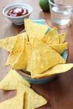 与辣调味汁的烤干酪辣味玉米片在一个蓝色碗 库存图片