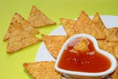 与辣调味汁的烤干酪辣味玉米片在心脏碗 免版税库存照片