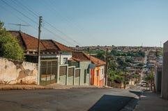 与边路墙壁和五颜六色的房子的下坡街道视图在São曼纽尔的一个晴天 库存图片