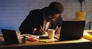 与运作在夜办公室的手提电脑和纸的年轻黑商人 他签署本文 ?? 股票录像
