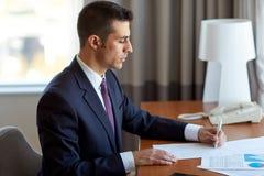 与运作在旅馆客房的纸的商人 免版税图库摄影