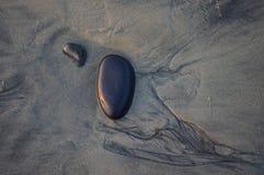 与运动的两块光滑的黑石头在沙子追踪了 图库摄影