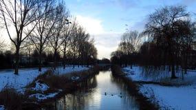 与运河、树和鸟运河的美好的积雪的冬天风景 库存照片