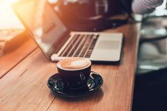 与运转在咖啡馆概念的膝上型计算机的拿铁咖啡 免版税库存照片