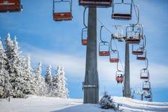 与运载小山的滑雪者的滑雪电缆车 免版税库存照片