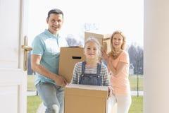 与进入新的家的纸板箱的愉快的家庭 库存照片
