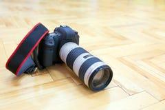 与远摄镜头的DSLR照相机在镶花地板上 免版税库存图片