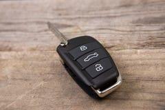 与远程警报控制的汽车钥匙在木书桌上 免版税库存照片