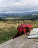 与远足地图和背包的长木凳 免版税库存照片