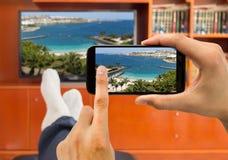 与连接的观看的照片巧妙的电视和智能手机之间 免版税图库摄影