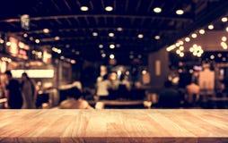与迷离光bokeh的木台式酒吧在黑暗的夜咖啡馆 免版税库存照片