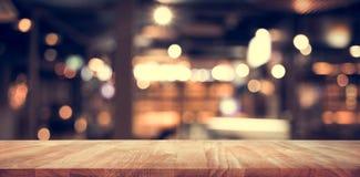 与迷离光bokeh的木台式酒吧在黑暗的夜咖啡馆 免版税库存图片