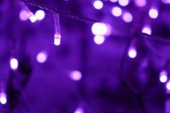 与迷离bokeh的发光的圣诞灯在照明节日 defocused 免版税库存照片