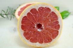 与迷迭香分支的切的红色葡萄柚在桌上 库存图片