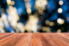 与迷离光的木桌 库存照片