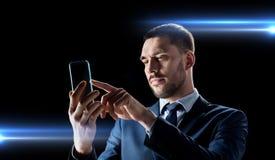 与透明智能手机的商人 免版税库存照片