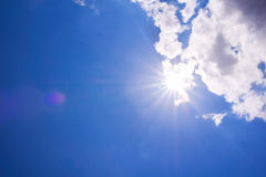 与透镜火光的现实光亮的太阳 蓝色覆盖天空 免版税库存照片