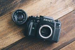 与透镜的Zenit品牌老影片DSLR照相机在一张木桌上 免版税库存照片
