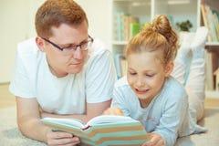 与逗人喜爱的女儿的年轻愉快的父亲看书在家 免版税库存图片