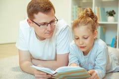 与逗人喜爱的女儿的年轻愉快的父亲看书在家 免版税图库摄影