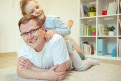 与逗人喜爱的女儿的年轻愉快的父亲看书在家 库存图片