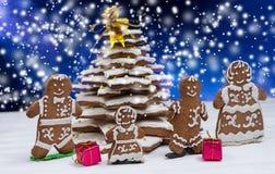 与逗人喜爱的姜饼家庭的可爱的自创姜饼圣诞树与礼物 库存图片
