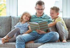与逗人喜爱的孩子的年轻愉快的父亲阅读书在家 库存照片
