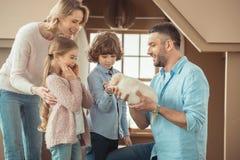 与逗人喜爱的拉布拉多小狗的年轻家庭在前面 免版税库存照片