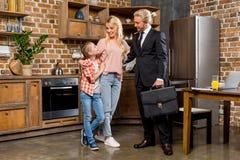 与逗人喜爱的矮小的一起站立女儿和的妻子的微笑的年轻商人 库存照片