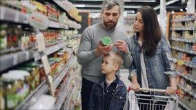 与逗人喜爱的矮小的儿子的已婚夫妇购物食物,他们采取玻璃从架子能和检查成份 影视素材