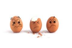 与逗人喜爱的面孔的三个鸡蛋 免版税库存照片