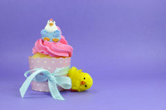 与逗人喜爱的鸡装饰的愉快的复活节桃红色,黄色和蓝色杯形蛋糕-复制空间 免版税库存照片
