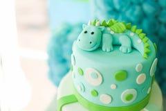 与逗人喜爱的龙的蓝色和绿色生日蛋糕 免版税库存图片