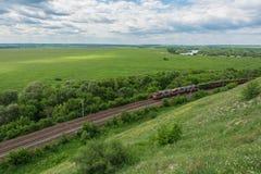 与通过由铁路的机车的货车在俄罗斯,沿典型的俄国风景,顶视图 图库摄影
