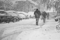 与通过的人的降雪的都市风景  免版税图库摄影