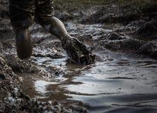 与通过飞溅和扯拽泥的脚的深泥泞的水 免版税库存图片