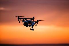 与遥控的Quadrocopter寄生虫 反对colorfull日落的黑暗的剪影 软绵绵地集中 被定调子的图象 免版税库存图片