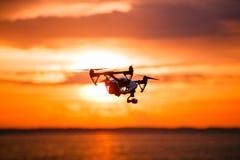 与遥控的Quadrocopter寄生虫 反对colorfull日落的黑暗的剪影 软绵绵地集中 被定调子的图象 免版税图库摄影