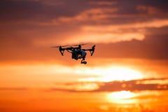 与遥控的Quadrocopter寄生虫 反对colorfull日落的黑暗的剪影 软绵绵地集中 被定调子的图象 免版税库存照片
